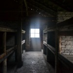 Birkenau barrack interior.  Several people crammed into the space fit for two.  Those at the top froze in winter, those at the bottom slept in mud