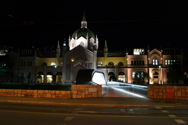 A bridge over the Miljacka river and the Academy of Fine Arts at night in Sarajevo