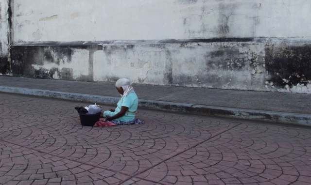 A woman sits on the stone tiles in the Nicaraguan city of Leon