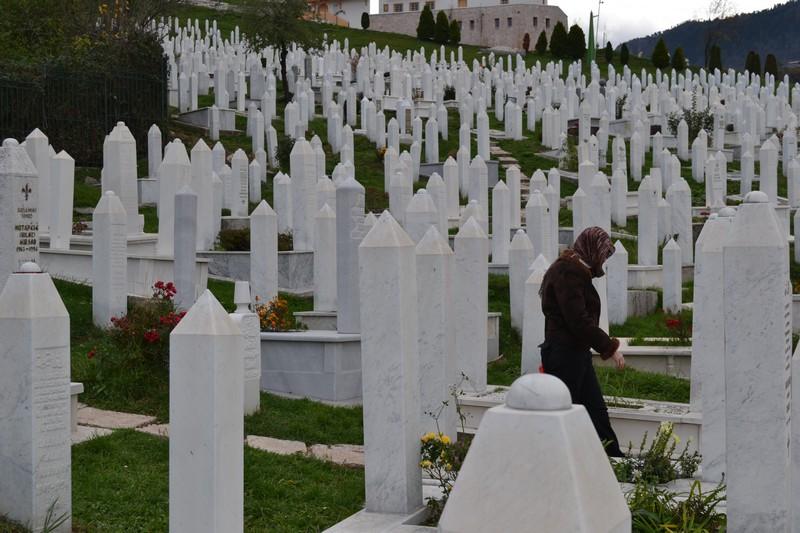 A woman in a headscarf walks through the Muslim graveyard in Sarajevo