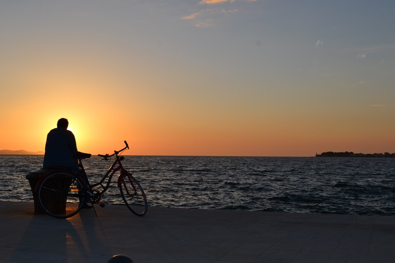 A man and his bike silhouetted against the Zadar sunset