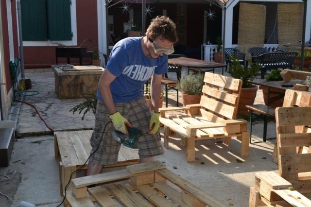 A man building wooden pallet furniture at a hostel